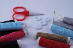 Sewing equipment. Roll of color threads, needle, measuring tape and white Royalty Free Stock Image