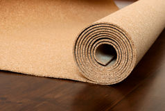 Roll of cork lies on a brown floor. The foor is made of pine and covered with semimatt lacquer stock photography