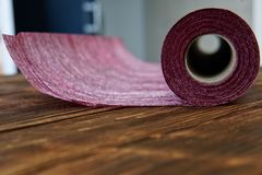 A roll of craft material from felt for home needlework lies in the workshop on pine boards royalty free stock photography