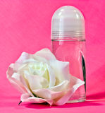 Roll On Deodorant. A glass container of roll on deodorant and a white silk rose Royalty Free Stock Image