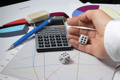 Roll of the Dice. A hand rolls a pair of dice over financial charts as if leaving finances up to chance. There is a calculator, pencil and eraser in the photo Royalty Free Stock Image