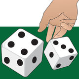 A Roll of the Dice. Hand is tossing a couple of dice onto a green surface Stock Photo