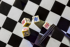 Roll the dice. Poker dice on chessboard Royalty Free Stock Photography