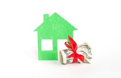 Roll of dollar with green home model Stock Images
