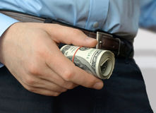 A roll of dollar in hand Stock Image