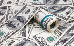 Roll dollars. Roll of dollars on a background of American dollar bills Stock Photos