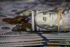 A roll of dollars on the background of scattered hundred dollar bills and various coins stock photos
