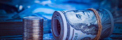 A roll of dollars with coins on the background of scattered one hundred dollar bills in blue light.  stock photos