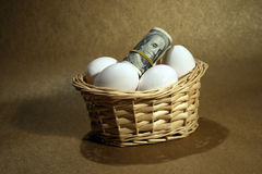 Roll of dollars with eggs Royalty Free Stock Images