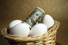 Roll of dollars with eggs Stock Image