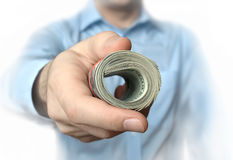 A roll of dollars in hand Stock Photo