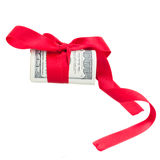 Roll of dollars with red bow. And ribbon isolated on white background Royalty Free Stock Photography