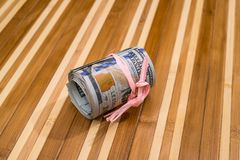 Roll of dollars on wooden. Background Stock Photography