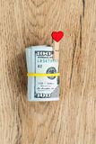Roll of dollars with yellow rubber. Roll of dollars tied yellow rubber, with a gift in the form clothespin of a red heart on a wooden table Stock Photography