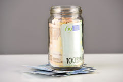 Roll of euro banknotes in a money jar Royalty Free Stock Images