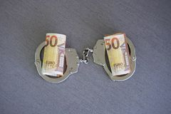 Handcuffs on and twisted money. Top view. stock images