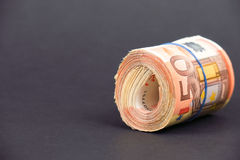 Roll of euro money. Rolled up 50 euro bills held together by an elastic band - copy space to the left Royalty Free Stock Photos
