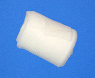Roll of first aid gauze. A single roll of first aid gauze on a blue background Royalty Free Stock Image