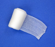 Roll of first aid gauze unrolling. A roll of new first aid gauze unrolling onto a blue background Royalty Free Stock Photography