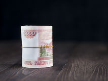 Roll of five thousandth rubles notes on wooden background Royalty Free Stock Photo