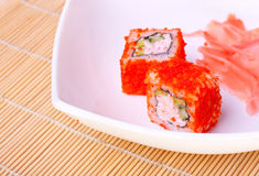 Roll with flying fish roe. On a white plate Royalty Free Stock Photography