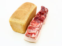 Roll of fresh bread and the big piece. Of fat with meat on a white background Stock Images
