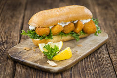 Roll with fried Fish Sticks (close-up shot) Stock Image