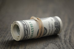 Roll of hundred dollar bills on wooden table Royalty Free Stock Photos