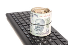 Roll of Indian Currency Rupee Notes on computer keyboard Royalty Free Stock Photo