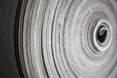 Roll of jeans cloth. The drapery of jeans rolled up in a cloth factory Stock Photos
