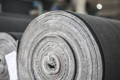 Roll of jeans cloth. The drapery of jeans rolled up in a cloth factory Royalty Free Stock Images