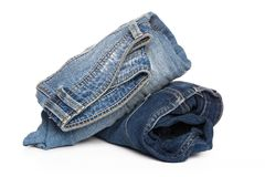 Roll light blue jeans closeup. Roll jeans isolated on white background stock photography