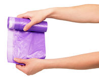 Roll lilac garbage packages in female hands isolated on white. Royalty Free Stock Photography