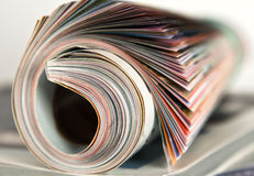 Roll of magazine on white background Stock Photo