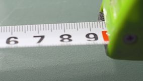 Roll of measuring tape on white background - macro stock video footage