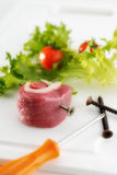 Roll of meat skewered on a long screw. A roll of raw meat and lattuce leaves and tomatoes on a white background, the meat is skewered on a long screw and there Royalty Free Stock Photography