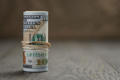 Roll of new style hundred dollar bills stand on Stock Images
