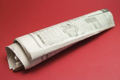 Roll news paper on red Stock Images