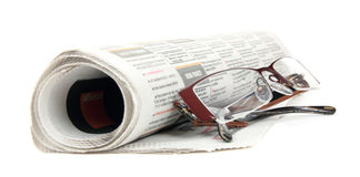 Roll of newspapers with eyeglasse. S , isolated on white background stock photography