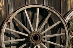 Roll no more. Old wagon wheel leaning against barn stock photography