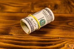Roll of the one hundred dollar bills with rubber on wooden table. Roll of one hundred dollar bills with rubber on rustic wooden table Royalty Free Stock Image