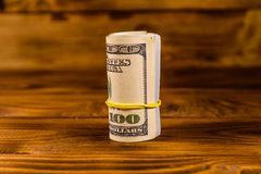 Roll of the one hundred dollar bills with rubber on wooden table. Roll of one hundred dollar bills with rubber on rustic wooden table Stock Image