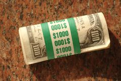 Roll of $ One Hundred dollar bills totalling $10 Royalty Free Stock Photography