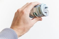 Roll of One Hundred Dollars in male hand isolated. On white background Royalty Free Stock Image