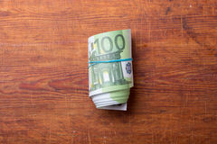 Roll of one hundred euro banknotes on wood. Background Royalty Free Stock Images