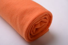 A roll of orange cotton cloth Stock Image