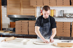 Roll out the dough. Closeup hand of chef baker in uniform blue apron cook pizza at kitchen Stock Images
