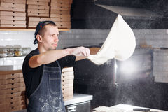 Roll out the dough. expanding cloud of flour. Closeup hand of chef baker in uniform blue apron cook pizza at kitchen Stock Image