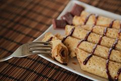 Roll pancake with chocolate on the plate stock images