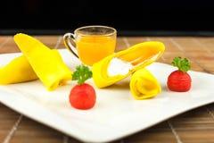 Roll pancake mango with mango juice on black background Royalty Free Stock Images